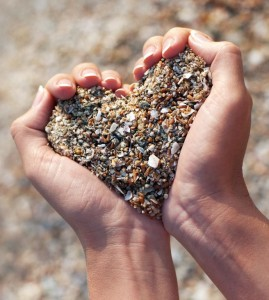 heart shaped hands holding sand