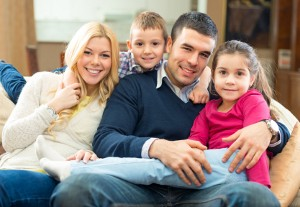 Photo of a family mother, father, son and daughter sitting on couch smiling Family therapy