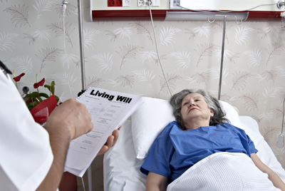 photo of woman in hospital bed with person holding a living will in the foreground