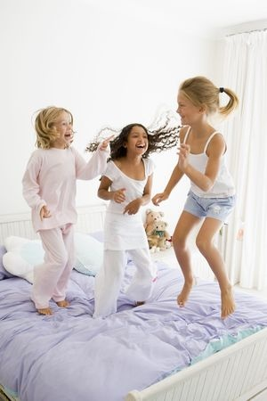 A day in the life of ptsd and trauma. kids playing and jumping on a bed.